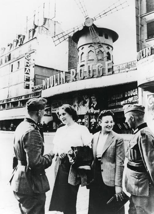 Немецкие солдаты разговаривают с француженками на фоне Мулен Руж во время оккупации Парижа. 1940г.