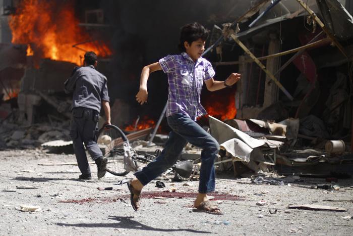Сирийский юноша пробегает мимо кровавого следа и останков упавшего самолета. 20 августа 2015г.