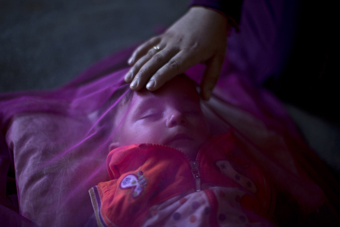 24-летняя беженка накрыла своео 7-месячного сын москитной сеткой. Они только что пересекли сирийскую границу. У девушки пропало в груди молоко, а денег, чтобы купить его нет. *Мы выжили при бомбежке в Сирии, а сейчас, я боюсь, мы погибнем от голода*.