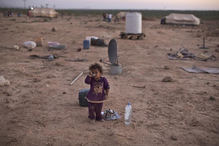 Ребенок пьет чай возле палатки, где живет его семья. Они покинули Сирию и сейчас находятся в Иордании. 26 августа 2015г.