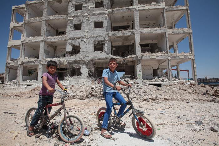 Дети позируют на своих велосипедах на фоне разрушенного здания в центре городе Кобан, Сирия. 20 июня 2015г.