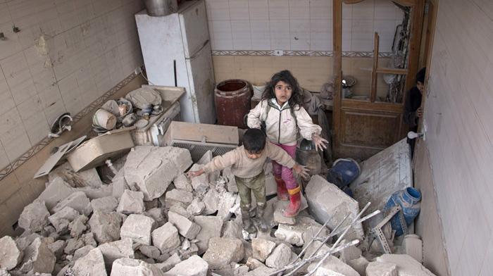 Сирийские дети пробираются по обломкам своего дома. Национальные силы бомбили с воздуха армию повстанцев, город Алеппо. 19 апреля 2015г.