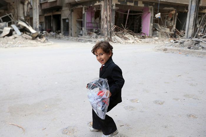 Мальчик несет сумку с новой одеждой перед праздником конца Рамадана. Окраины Дамаска, Сирия. 15 июля 2015г.