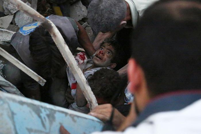 Сирийцы спасают раненого мальчика после авиационной атаки в городе Дума. 16 июня 2015г.