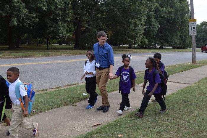 Учитель провожает домой детей, которые живут далеко от школы.