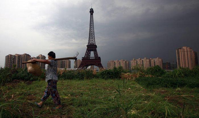 Фермер с граблями идет по грунтовой дороге мимо копии Эйфелевой башни в Тьяндученг, 1 августа 2013.