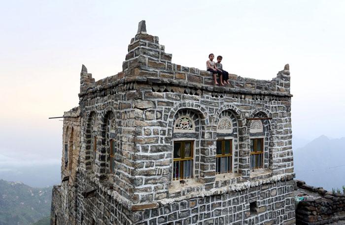 Мальчики сидят на крыше своего дома.  Фото: Abduljabbar Zeyad.