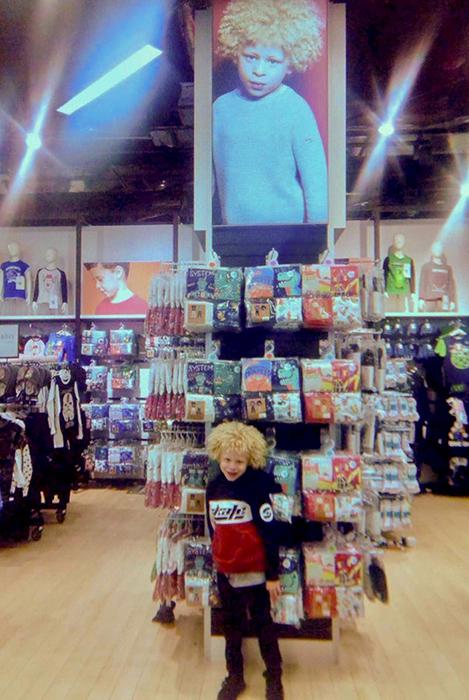 Элайджа в магазине рядом со своей фотографией.