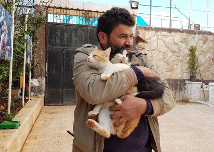 Мохаммед обнимает котов в своем приюте для животных.
