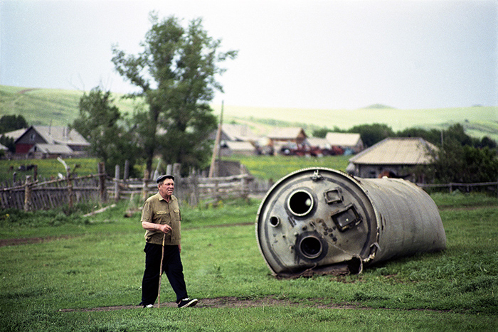 Местный житель идет мимо упавшей части ракеты. Фото: Jonas Bendiksen.