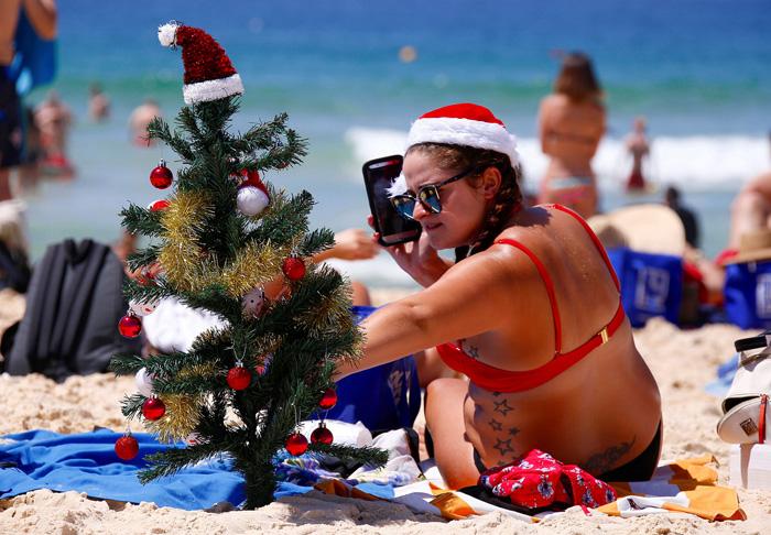Ирландка Денна Вудс укрепляет в песке маленькую елочку в рождественских декорациях на пляже Бонди. 25 декабря 2016. Фото: David Gray.