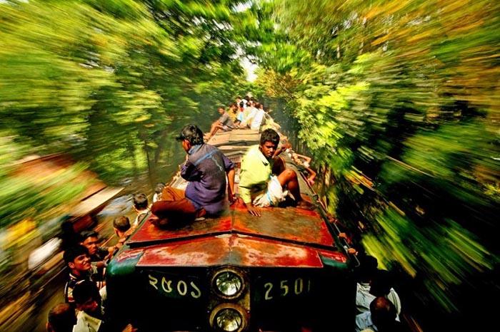 Некоторым пассажирам приходится ехать на подножке сбоку вагонов. Автор фото: GMB Akash.