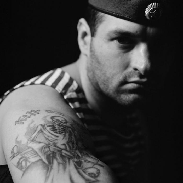 Игорь Мокров, ветеран двух чеченских кампаний позирует для портрета и показывает свою татуировку Kill 'em All.