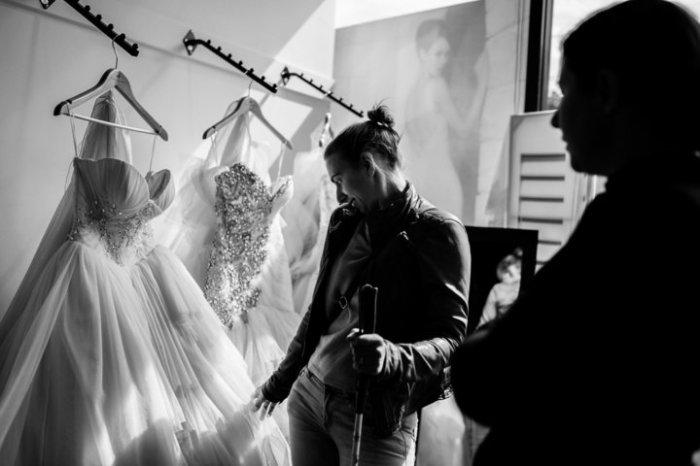 Стефани прикасается к свадебному платью, которое вынесли для нее,  то время как ее подруга в тени стоит, готовая помочь. Фото: James Day.