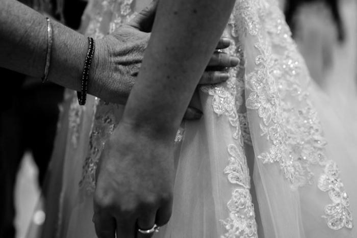 Мама пытается понять на ощупь, насколько хорошо платье сидит на ее дочери.  Фото: James Day.