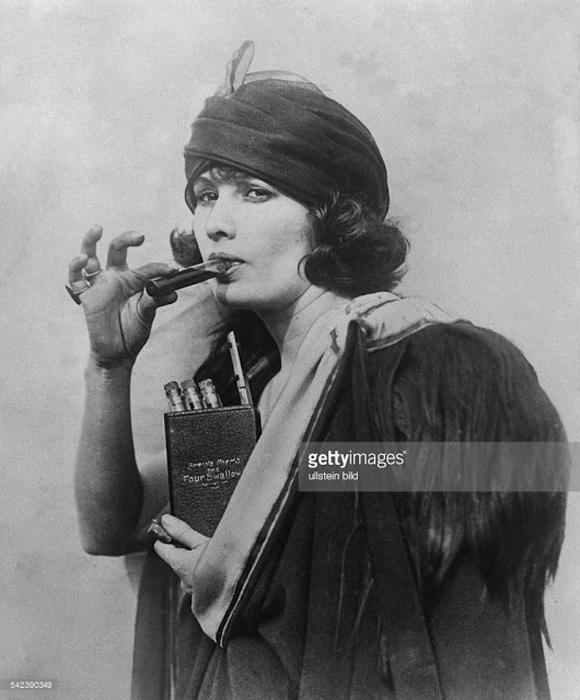 Женщина использует карманную книгу с надписью *Четыре глотка*, чтобы прятать в ней алкоголь во время сухого закона. 1920-е гг.