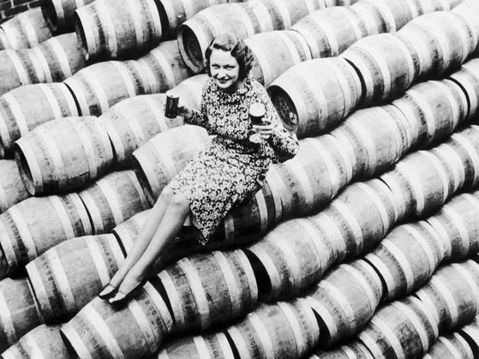 Однако всему нелепому рано или поздно приходит конец. Женщина сидит на бочках с пивом 1933 г.