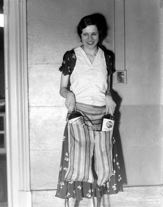 Эстелла Земон показывает накладной пояс-фартук, позволяющий пронести бутылки алкоголя мимо охранников. 18 марта 1931г. Фото: AP Photo.