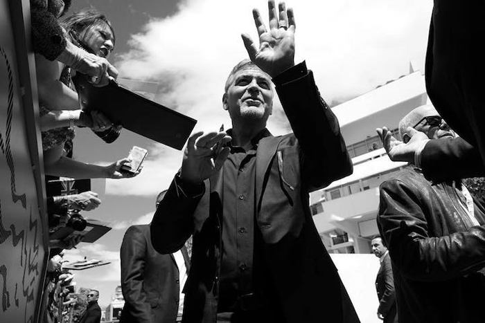 Джордж Клуни (George Clooney) раздает автографы перед посещением пресс-конференции к фильму *Денежный монстр*.