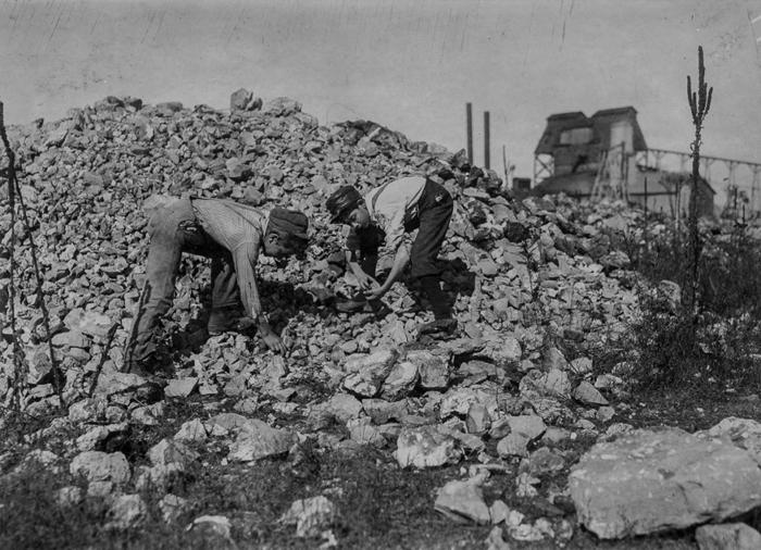 12-летние мальчики разбирают цинковые остатки, вывезенные из шахты в городе Аврора, Миссури.