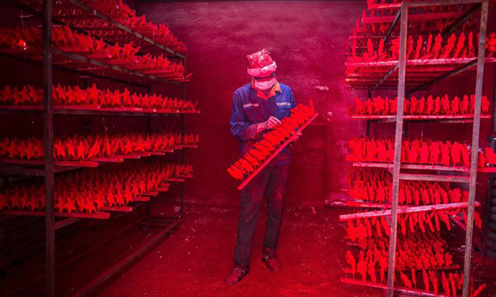 Два рабочих делают около 5 000 красных снеговиков в день.