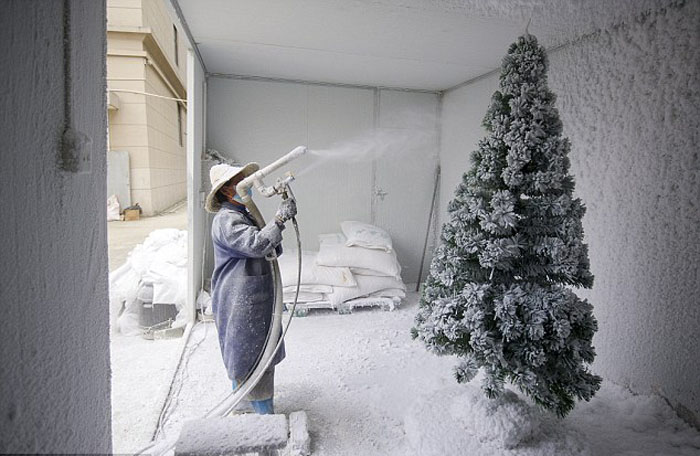 Рабочий покрывает елки искусственным снегом на заднем дворе фабрики.