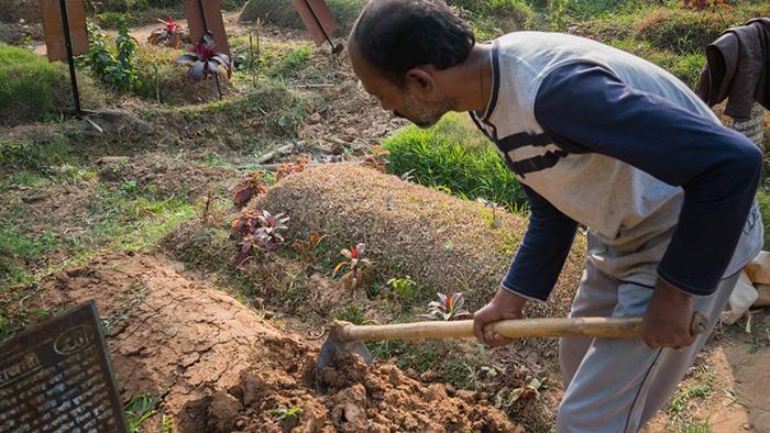 Мужчина ухаживает за могилой в Дакке. Фото: Amirul Rajiv.