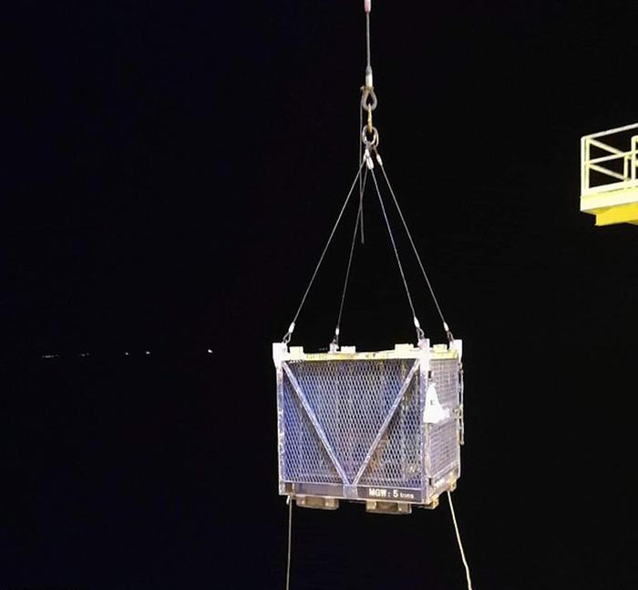 С помощью крана клетку подняли и перенесли на проходящее мимо судно.