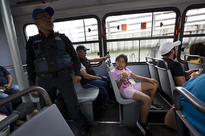 Полицейский офицер Хосе Осорио дель Анхель стоит дежурит в одном из автобусов, следующих из Истапалапа в центр Мехико.
