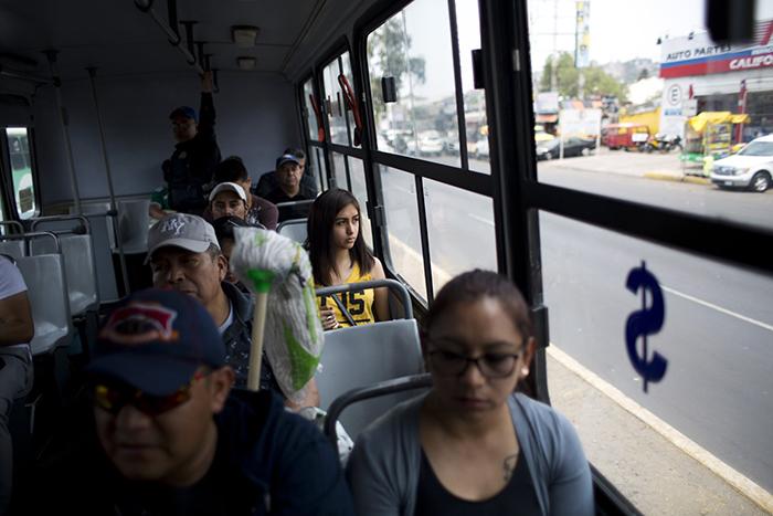 Полицейский Хосе Осорио дель Анхель стоит в глубине автобуса.