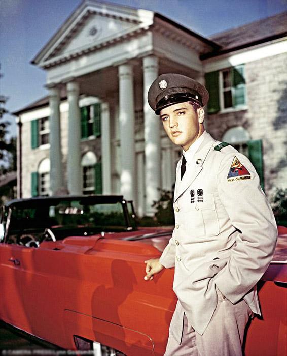 Элвис позирует в военной форме перед своим поместьем Грейсленд.