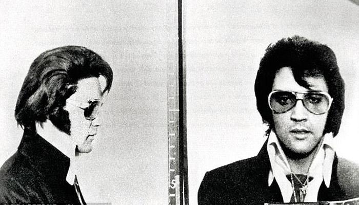 Элвис позирует со значком, который он получил от Денверской Полиции.