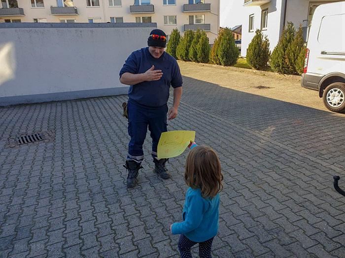 Девочка подарила пожарному свой рисунок.