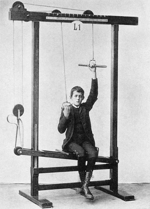 Парень с бутсах на высокой шнуровке растягивает мышцы рук, одновременно развивая мышцы спины.