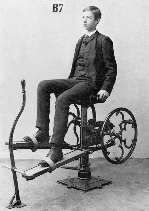 Хорошо одетый юноша использует аппарат, имитирующий езду на велосипеде.