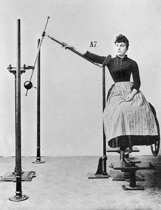 Девушка в платье и корсете показывает, как можно увеличить подвижность плечевого сустава.