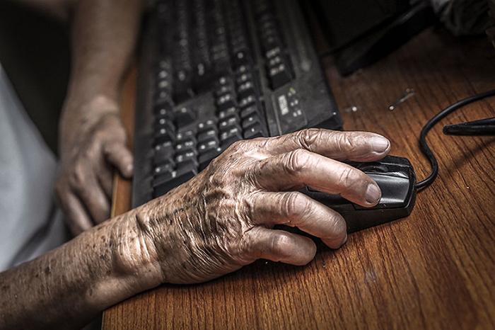 Дедушка сам учится пользоваться компьютером.  Фото: Hạ My Photography.