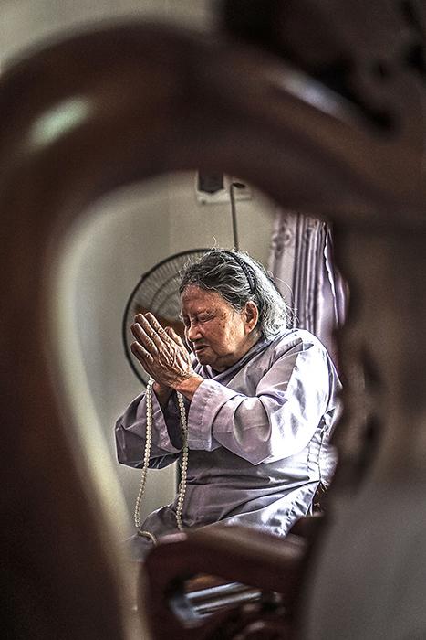 Бабушка молится за здоровье всей семьи.  Фото: Hạ My Photography.