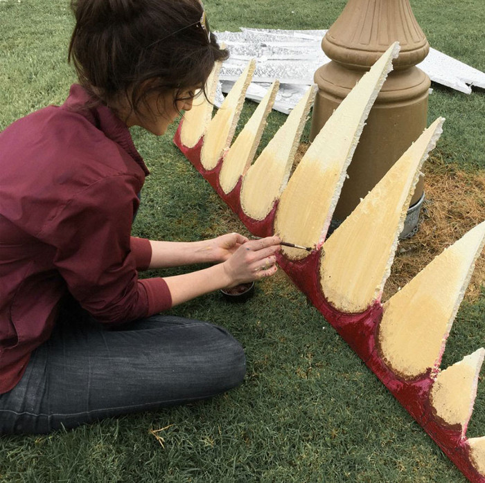 Christine McConnell раскрашивает клыки и зубы, сидя в саду.