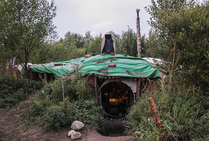 Круглый вход в землянку и колонка на крыше, из которой доносятся аудиозаписи чтения книг. Фото: genamartynov.