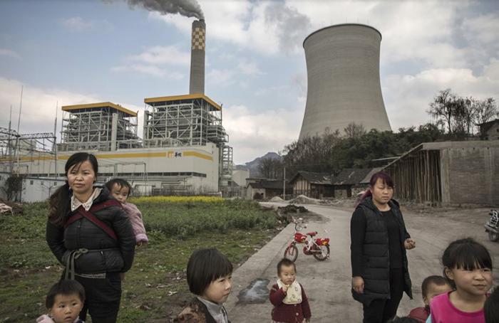 Жители деревни рядом с недавно построенным заводом, загрязняющим воздух. Китай.