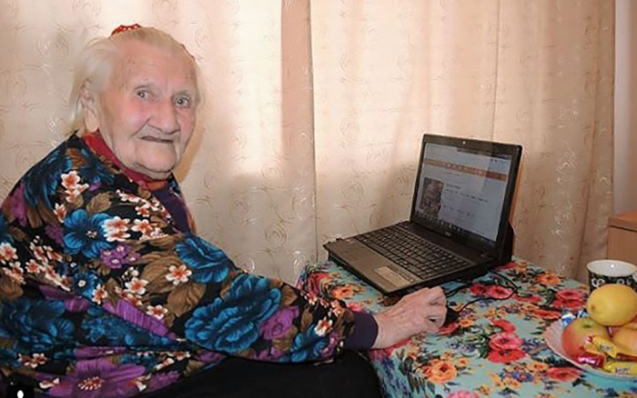 Бабушка с ноутбуком у себя в комнате.