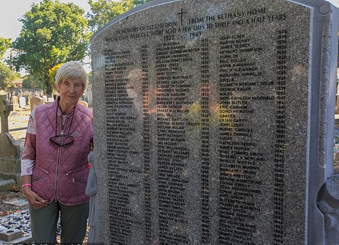 Эйлин рядом с памятником, на котором выбиты имена 222 малышей, похороненных рядом с интернатом, в котором выросла сама Эйлин.