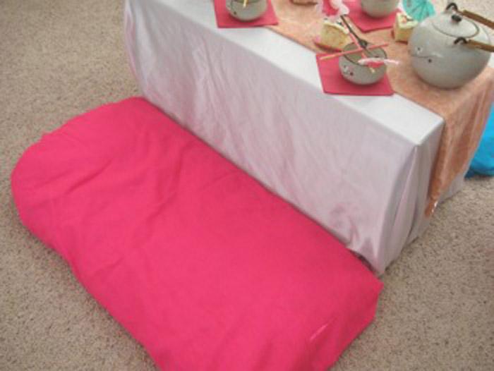 Стол мама сделала из обычной коробки, покрыла ее скатертью, а рядом положила обычные подушки.