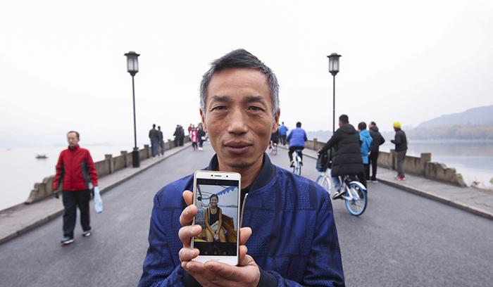 Сю показывает фотографию Кэти на своем мобильном телефоне, стоя на Сломанном мосту.