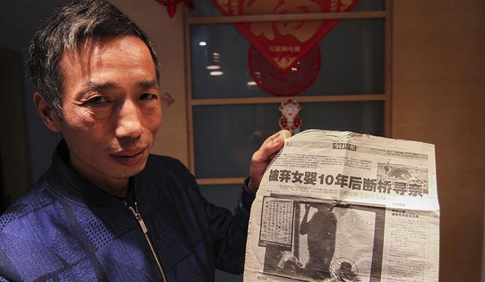 Сю держит газету, в которой рассказывается о том, что они ищут свою дочь. 2005 год.