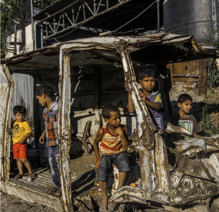 Палестинские дети играют с останками машины в городе Газа. 5 августа 2015 г.  Фото: Emad Samir Nassar.