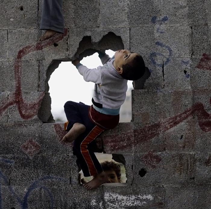 Мальчики играют на стене в окрестностях лагеря для беженцев на западе Газа.  Фото: Emad Samir Nassar.