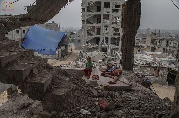 Дети из Аль-Атавна сидят на руинах своего дома, который был разрушен во время конфликта между Израилем и Хамасом. 25 февраля 2016 г.  Фото: Emad Samir Nassar.