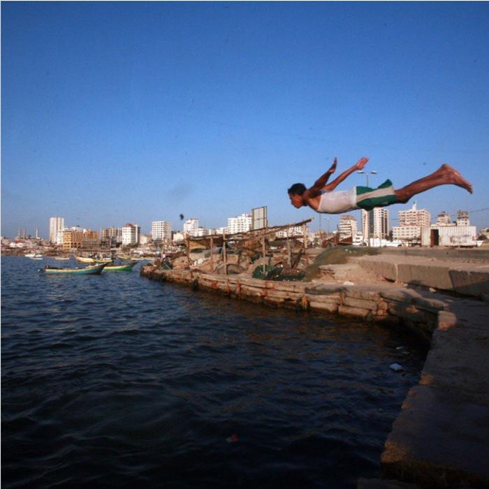 Мальчик прыгает в воду.  Фото: Emad Samir Nassar.